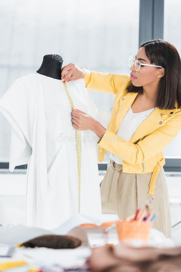 Молодая женщина держа измеряя ленту и работая с куклой внутри помещения стоковая фотография rf