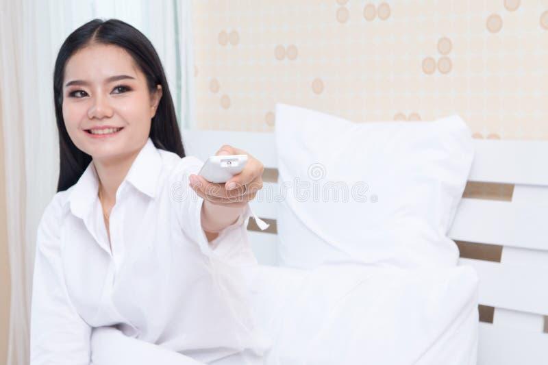 Молодая женщина держа дистанционное управление кондиционера воздуха, изолированное на белой предпосылке стоковые изображения rf