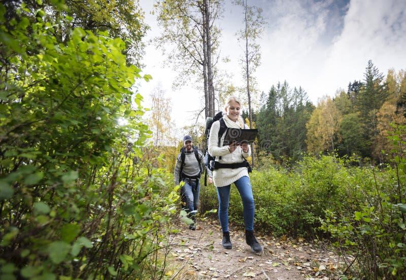 Молодая женщина держа карту пока пеший туризм с другом стоковые фото