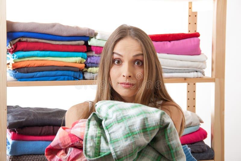 Молодая женщина держа кучу одежд стоковое изображение