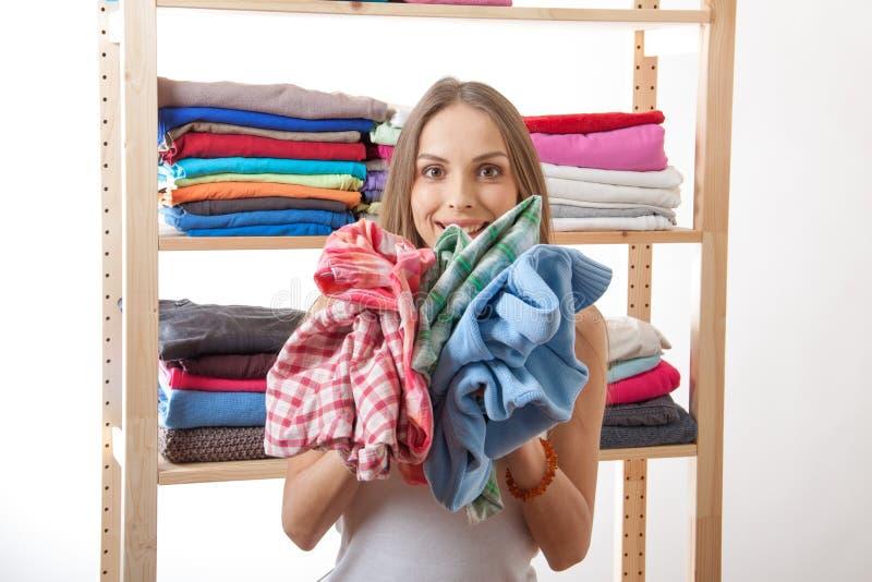 Молодая женщина держа кучу одежд стоковое фото