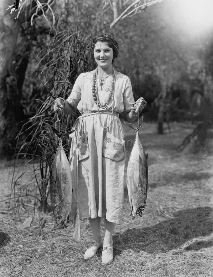 Молодая женщина держа 2 огромных рыб (все показанные люди более длинные живущие и никакое имущество не существует Гарантии постав стоковое изображение