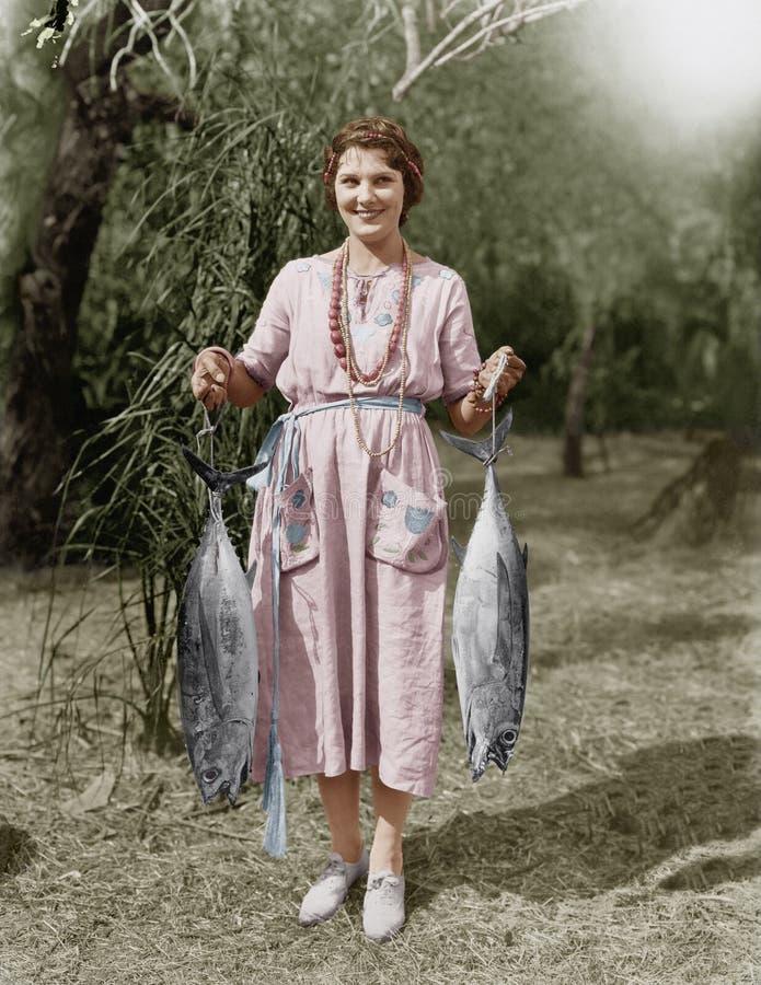 Молодая женщина держа 2 огромных рыб (все показанные люди более длинные живущие и никакое имущество не существует Гарантии постав стоковые фотографии rf