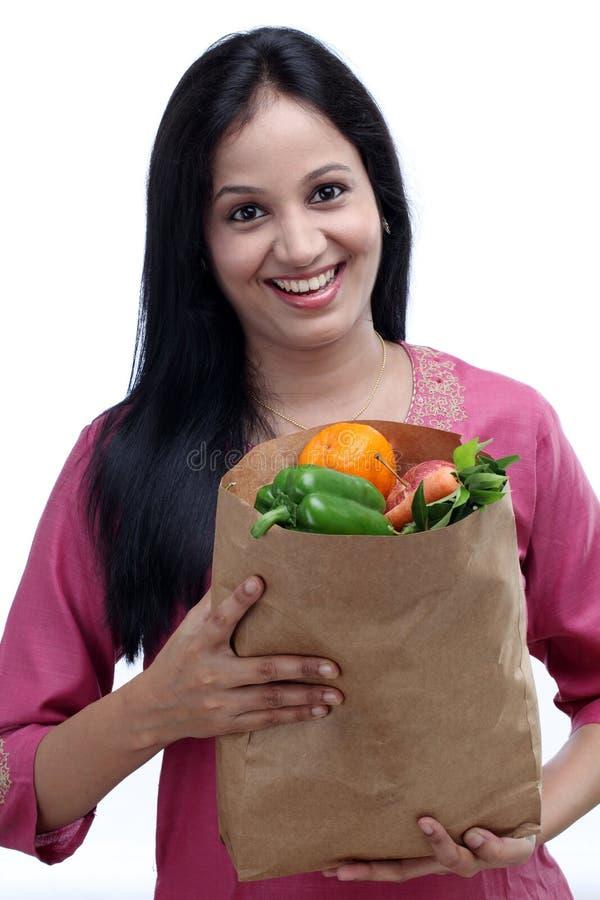 Молодая женщина держа продуктовую сумку стоковое изображение