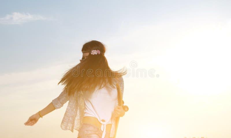Молодая женщина держа скейтборд в ее руках _ стоковые фото
