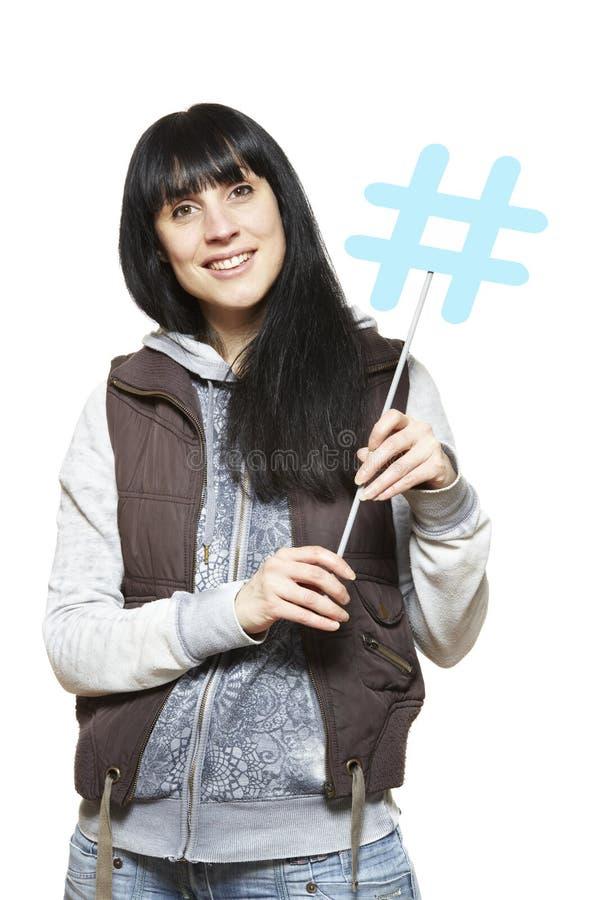 Молодая женщина держа социальный усмехаться знака средств стоковое фото