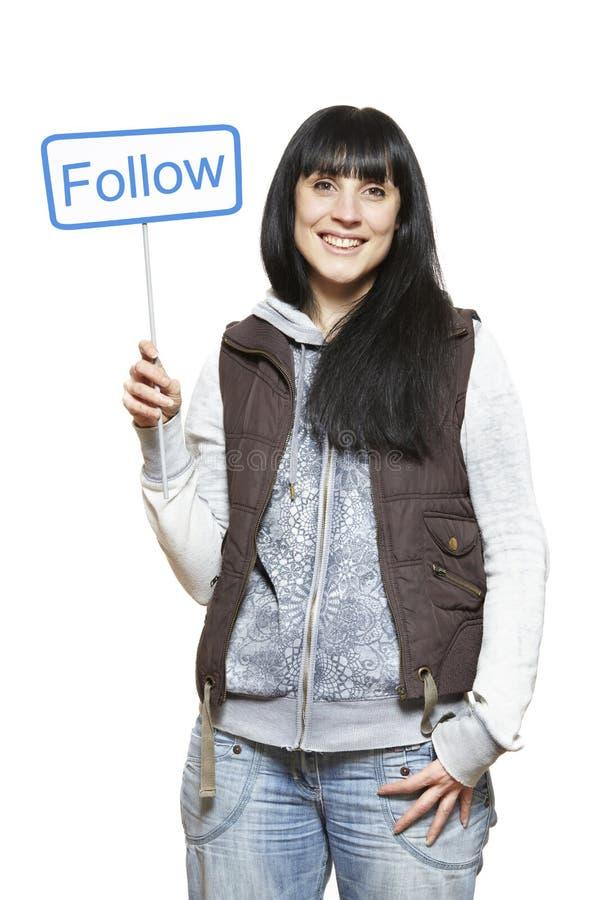 Молодая женщина держа социальные средства подписывает усмехаться стоковая фотография rf