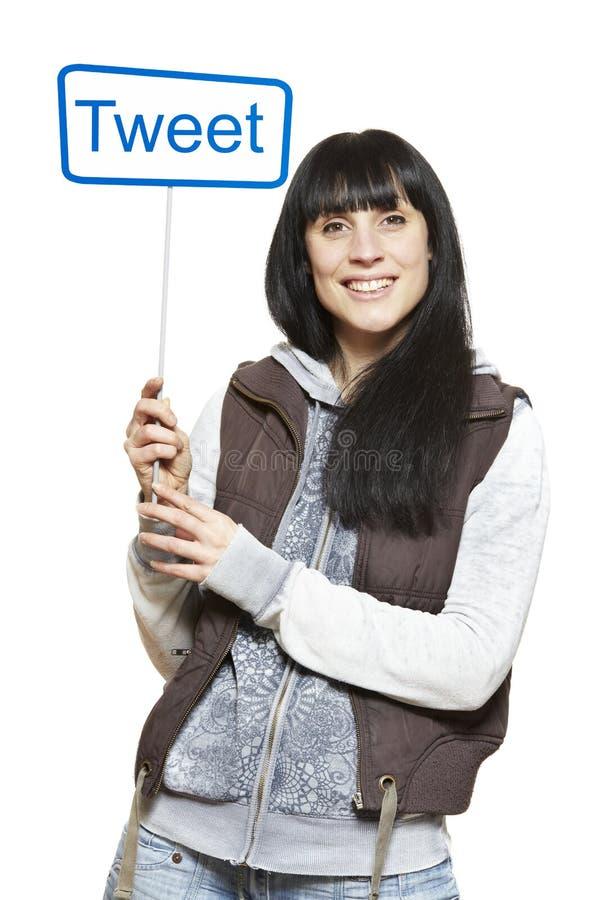 Молодая женщина держа социальные средства подписывает усмехаться стоковое изображение