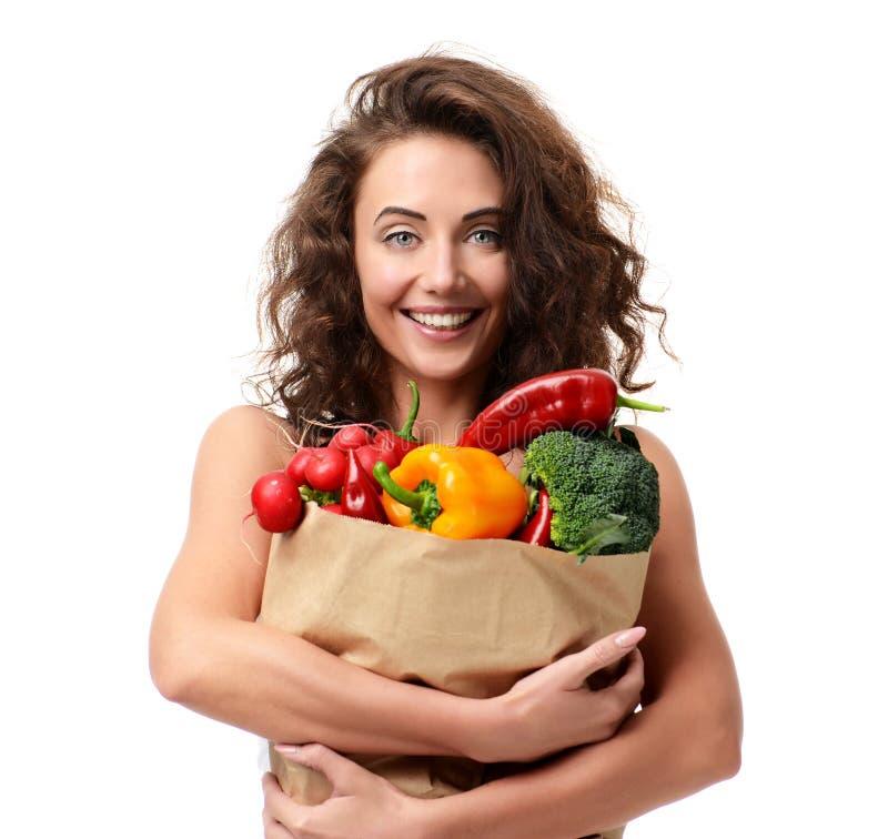 Молодая женщина держа хозяйственную сумку бакалеи бумажную полный свежего veg стоковые фотографии rf