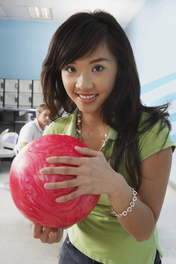 Молодая женщина держа шарик на кегельбане стоковое изображение