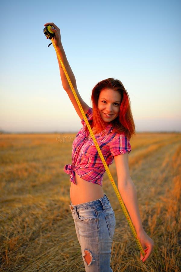 Молодая женщина держит рулетку tapeline в руки на поле стоковые изображения