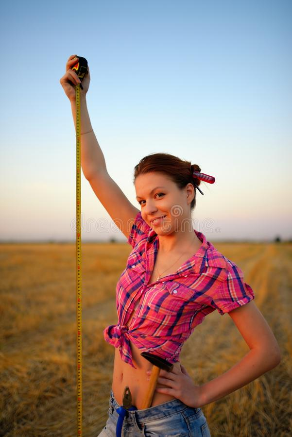 Молодая женщина держит рулетку tapeline в руки на поле стоковое фото rf