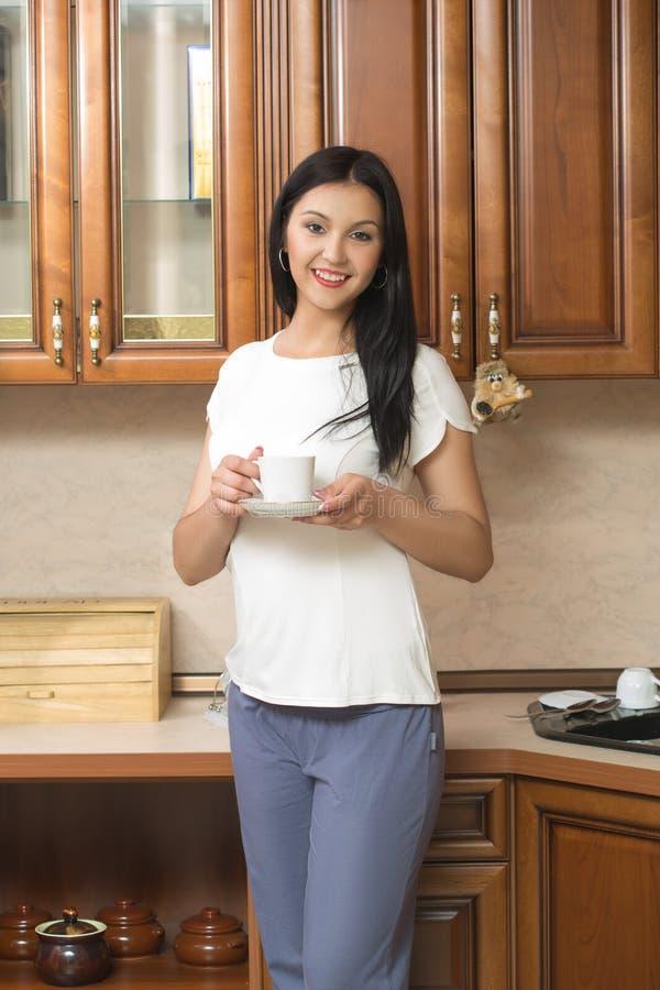 Молодая женщина держит чашку с кофе или чаем против стоковое фото