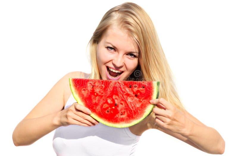 Молодая женщина есть большую ягоду арбуза куска стоковые фото