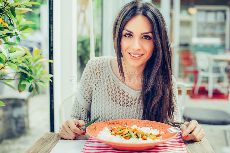 Молодая женщина есть китайскую еду в ресторане, имеющ ее lunc стоковое фото rf