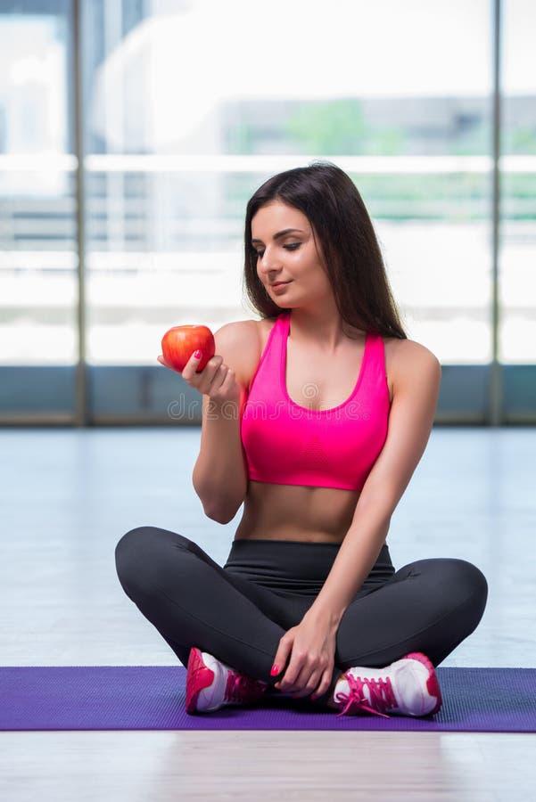 Молодая женщина есть красное яблоко в концепции здоровья стоковая фотография rf