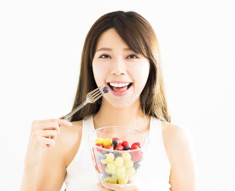 Молодая женщина есть свежие фрукты стоковые изображения
