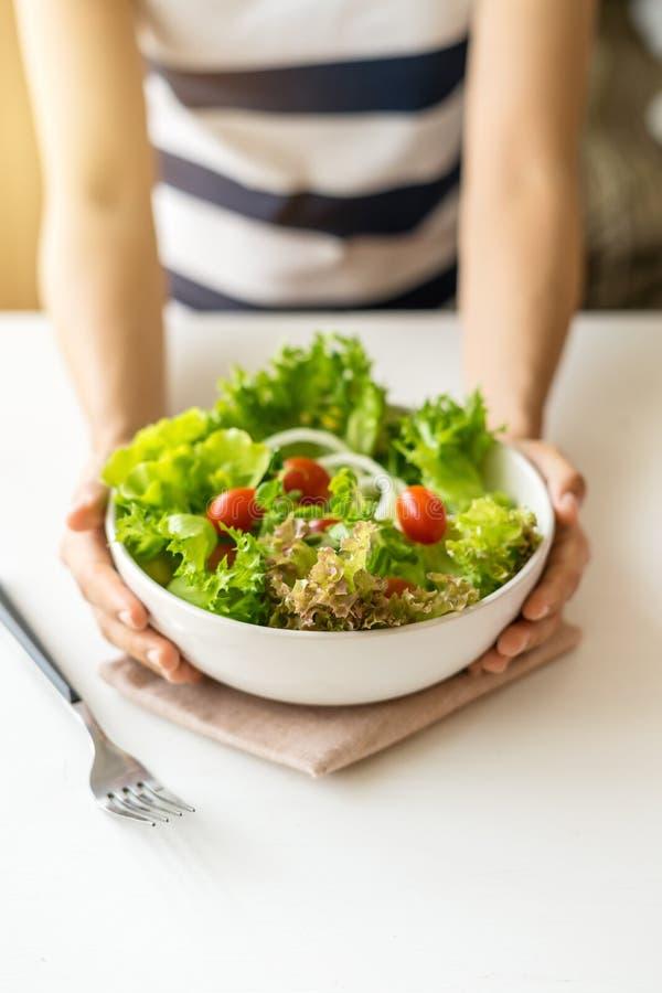 Молодая женщина есть свежий органический вегетарианский салат стоковое изображение rf