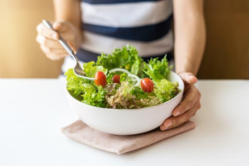 Молодая женщина есть свежий органический вегетарианский салат стоковая фотография rf