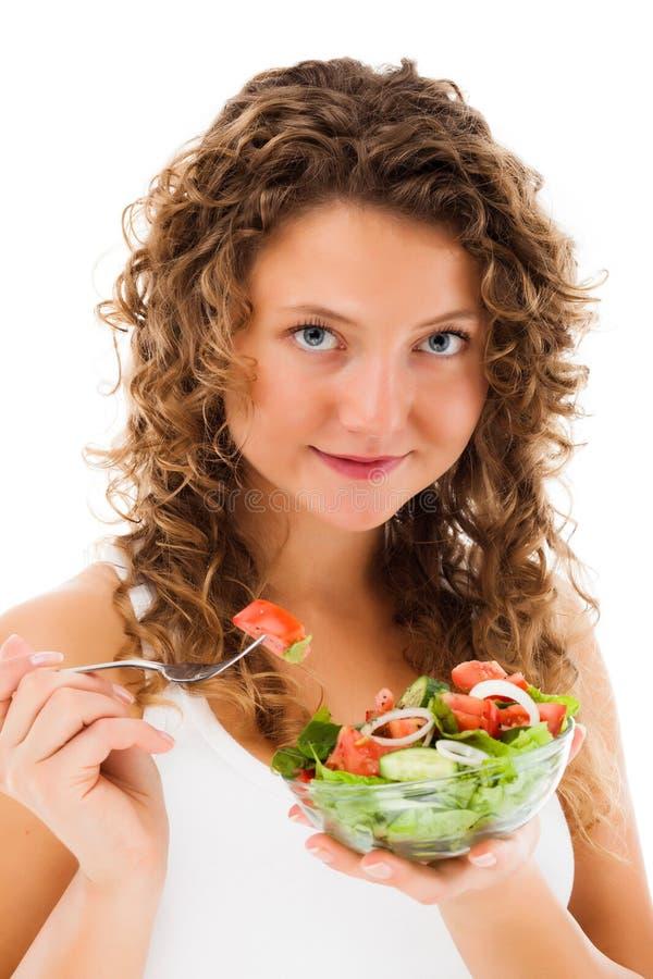 Молодая женщина есть vegetable салат на белой предпосылке стоковая фотография