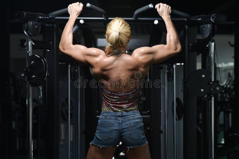Молодая женщина делая задние тренировки в спортзале стоковая фотография