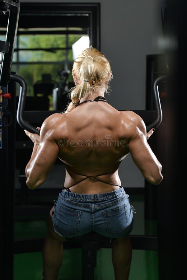 Молодая женщина делая задние тренировки в спортзале стоковые фото