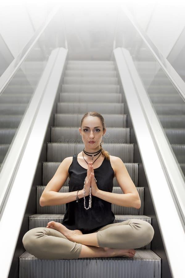 Молодая женщина делая йогу на эскалаторе, сидя в позиции лотоса Стресс освобождает концепцию стоковые изображения