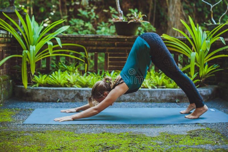 Молодая женщина делая йогу снаружи в окружающей среде стоковая фотография