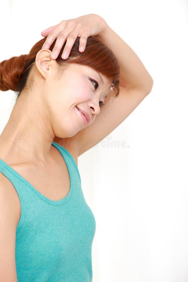 Молодая женщина делая простирание шеи собственной личности стоковое изображение