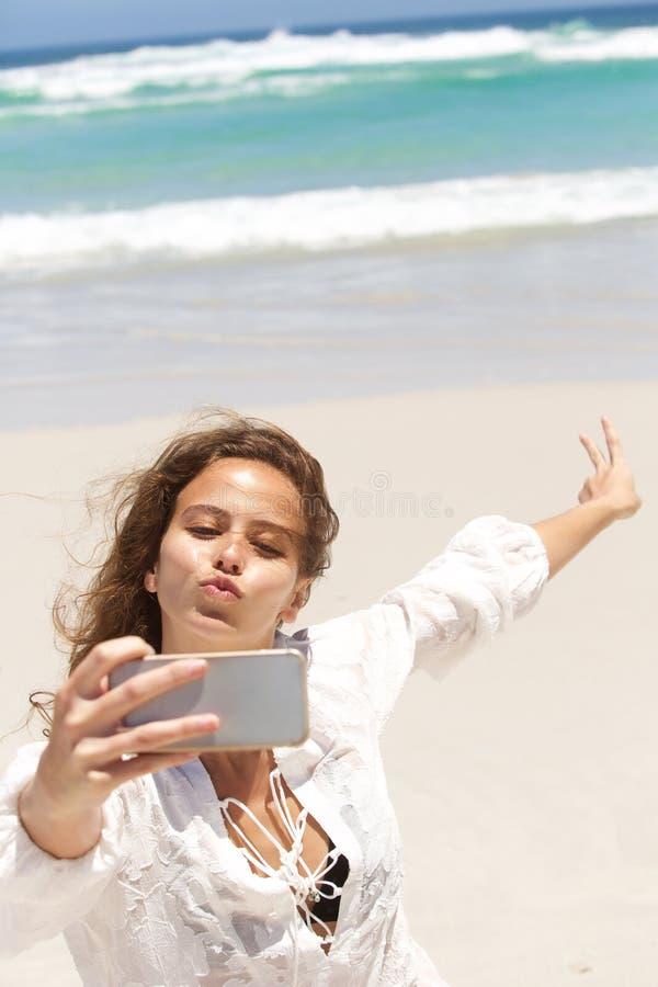 Молодая женщина делая смешную сторону пока принимающ selfie на пляж стоковые изображения