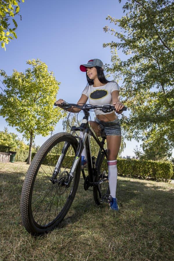 Молодая женщина делая спорт на велосипеде стоковое фото rf