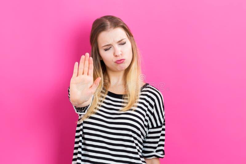 Молодая женщина делая стоп представить на розовой предпосылке стоковое фото