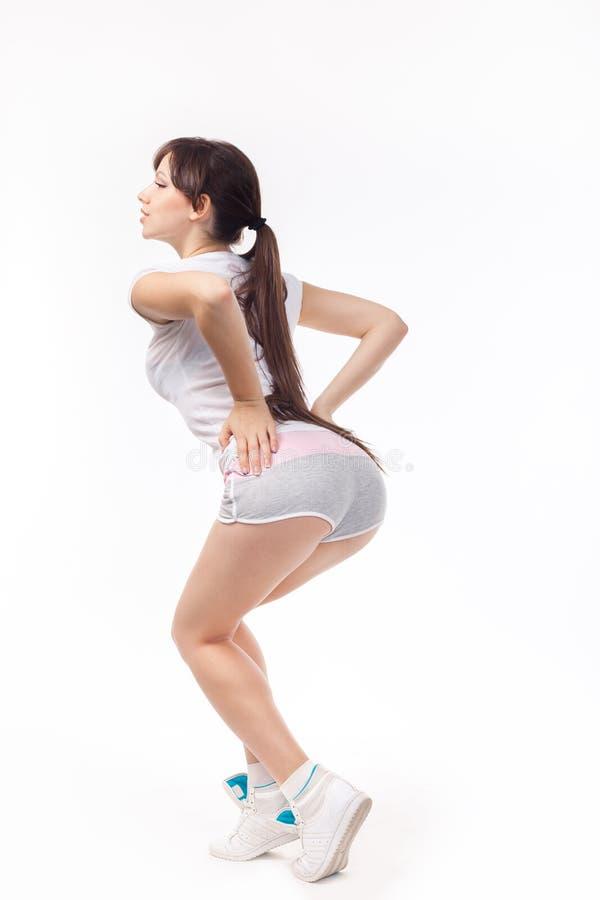 Молодая женщина делая тренировку сидеть на корточках изолированную на белой предпосылке стоковое фото rf