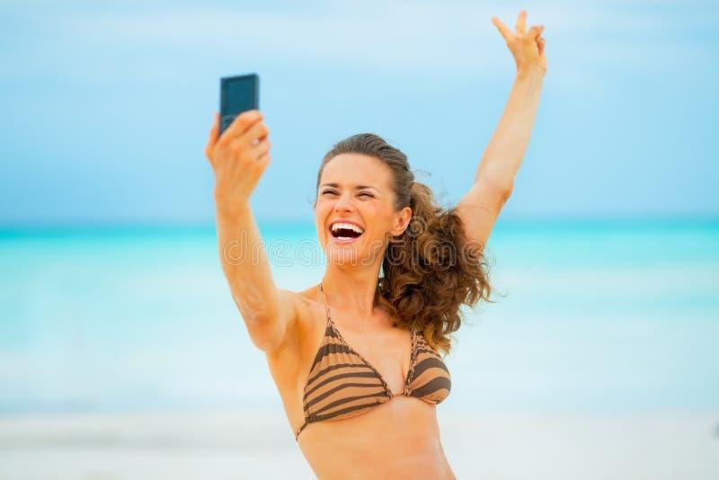 Молодая женщина делая selfie на пляже стоковые фото
