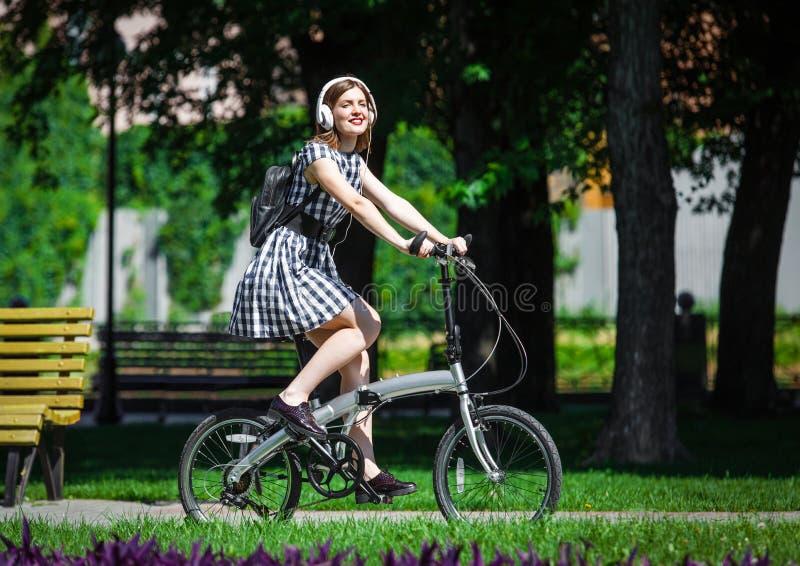 Молодая женщина едет велосипед в парке стоковая фотография