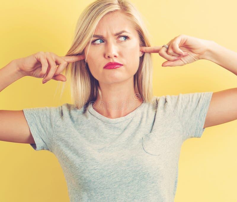 Молодая женщина затыкая ее уши стоковая фотография