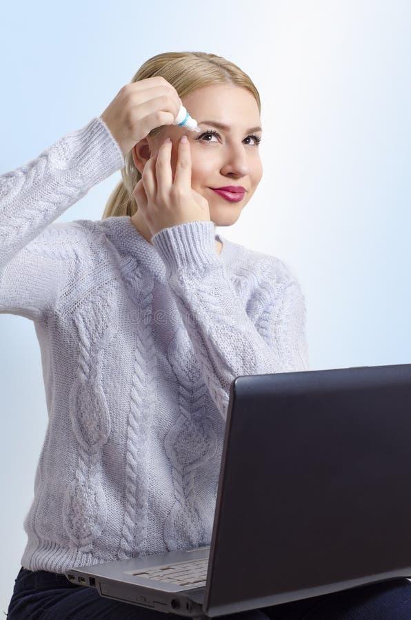 Молодая женщина защищая ее глаза и зрение пока работающ на компьютере стоковые фотографии rf
