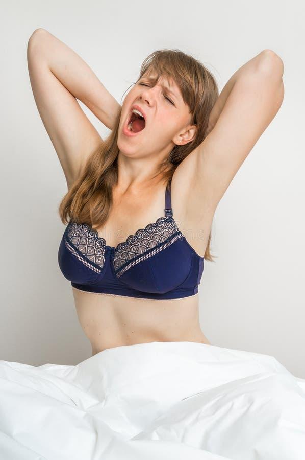 Молодая женщина зевает в кровати после спать стоковое фото rf