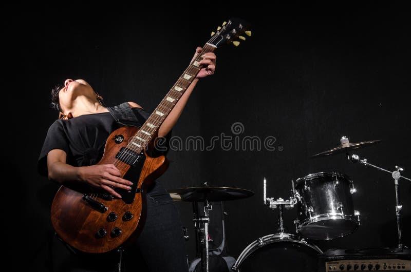 Молодая женщина играя гитару во время стоковая фотография
