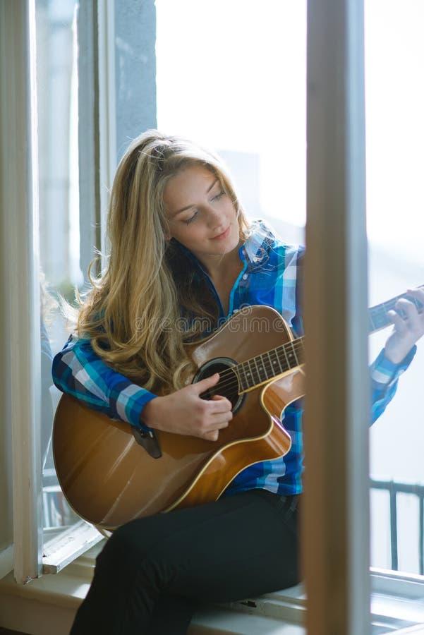 Молодая женщина играя гитару на окне стоковое изображение