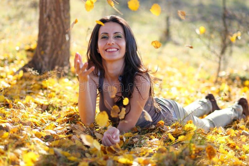 Молодая женщина играя с листьями стоковые фотографии rf