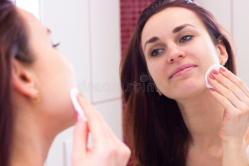 Молодая женщина извлекая состав в ванной комнате стоковое изображение