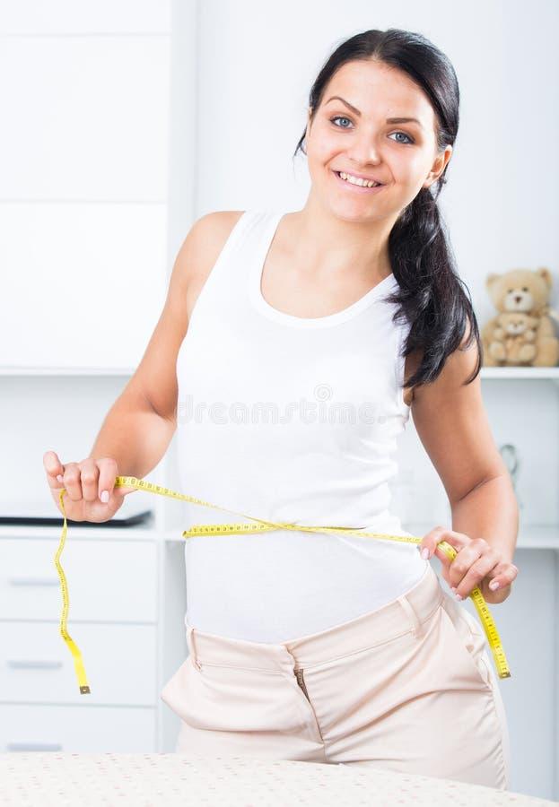 Молодая женщина измеряет талию стоковая фотография rf