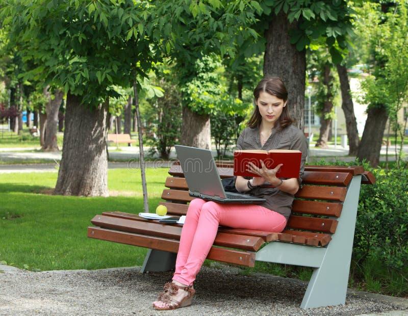 Молодая женщина изучая в парке стоковое изображение rf