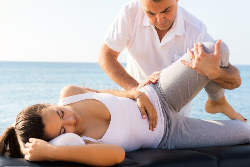 Молодая женщина имея osteopathic обработку ноги и бедренной кости outdoors стоковые изображения