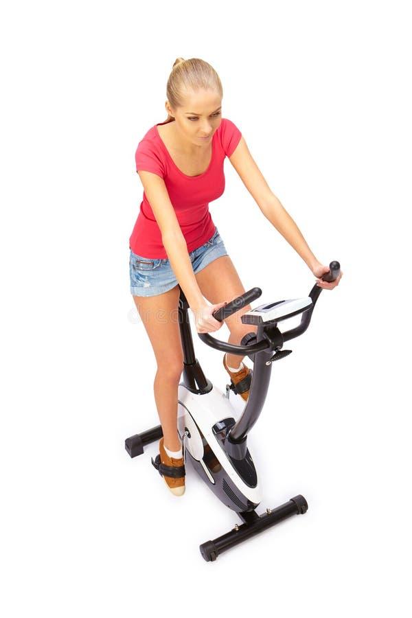 Молодая женщина использует неподвижного тренера велосипеда стоковая фотография