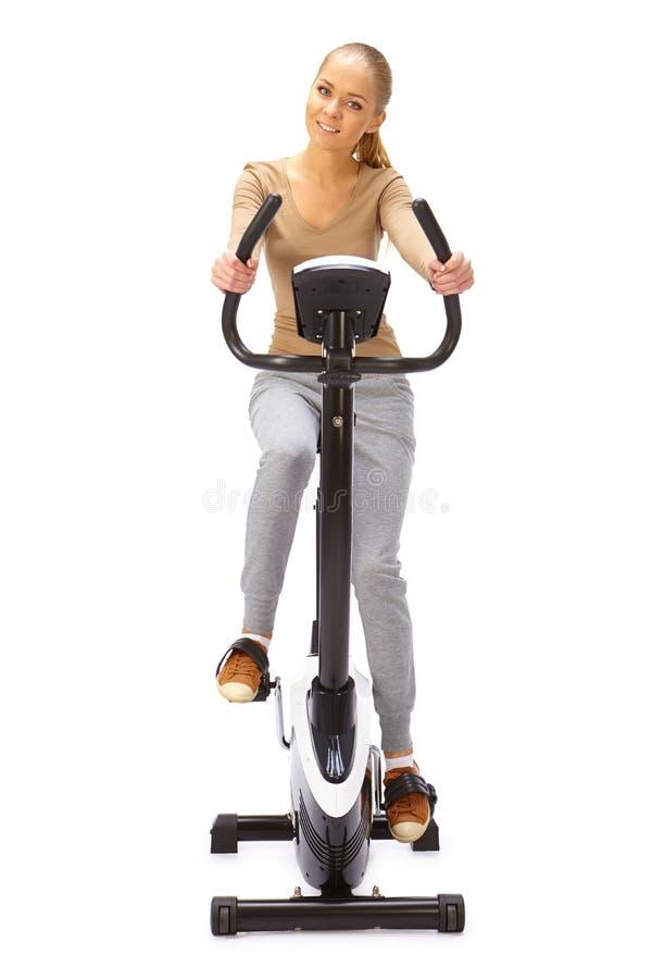 Молодая женщина использует неподвижного тренера велосипеда стоковое фото rf