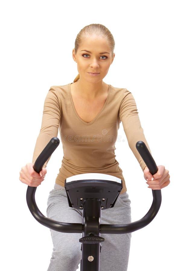 Молодая женщина использует неподвижного тренера велосипеда стоковое изображение