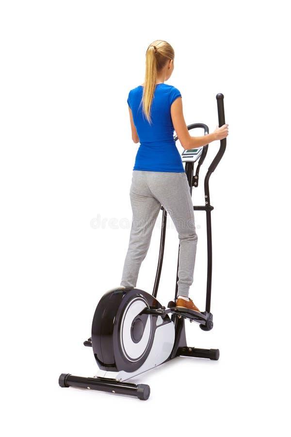 Молодая женщина использует эллиптического перекрестного тренера стоковая фотография rf
