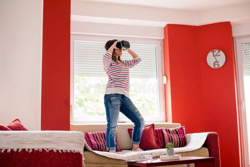Молодая женщина использует VR гуглит на ее доме стоковые фотографии rf